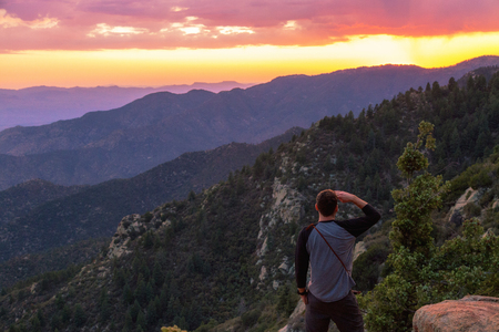 Male tourist with hand above eyes looking out over a colorful sunset on a mountain range in eastern Arizona, United States
