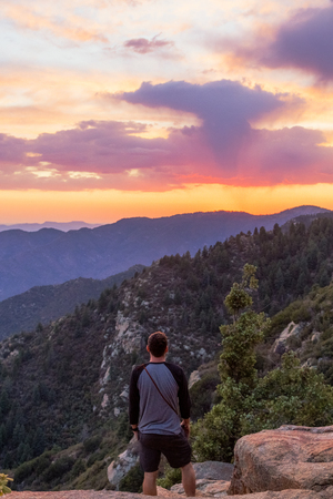 Back of a man looking out over a colorful sunset on Mt Graham in the Coronado National Forest in eastern Arizona
