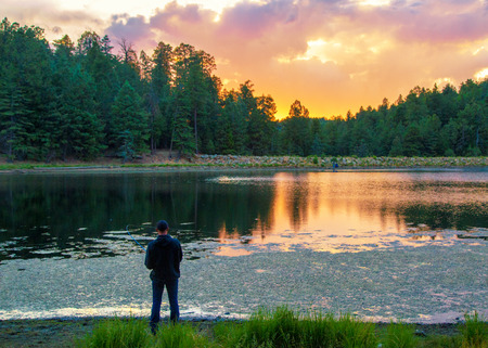 Man fishing on the shore of Riggs Flat lake on Mount Graham at sunset