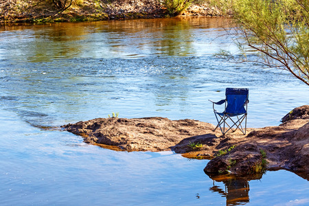 Empty chair sitting on bank of the Salt River in Mesa, Arizona
