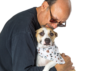 Adult male holding a scared mixed breed rescue dog in his arms