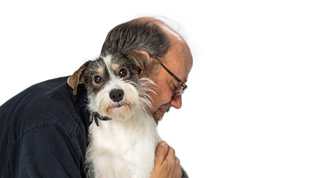 Adult male hugging a cute wire-haired nixed small terrier breed dog that is looking at the camera over white Reklamní fotografie