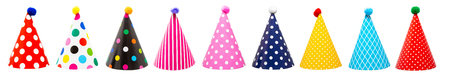 Row of nine colorful festive birthday party hats with different patterns and pom-poms Stock Photo