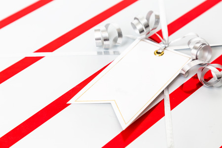 Closeup of wrapped Christmas present with ribbon and room for text in blank gift tag