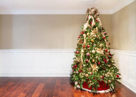 Geschmückter Weihnachtsbaum in der Ecke des leeren Wohnzimmers Standard-Bild
