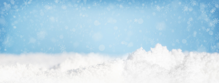Snow piles on ground and falling in blue sky. Stock Photo