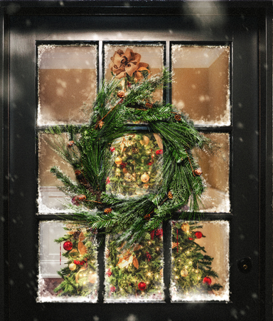 View looking into home with illuminated Christmas tree through door window with wreath and snow