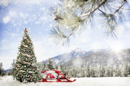 Christmas tree and Santa Claus sleigh with gifts in snowy winter outdoor scene in forest with snow-capped mountains.