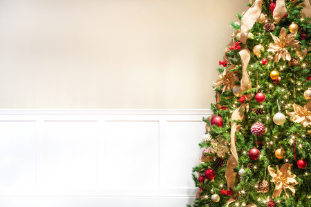 Closeup of decorated Christmas tree with room for text or image mockup on blank wall Foto de archivo