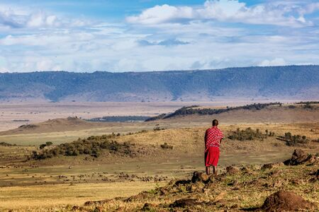 Authentic Maasai tribe member male standing in the middle of the Mara Triangle Conservency looking out over the beautiful rolling hillside land  Stock fotó