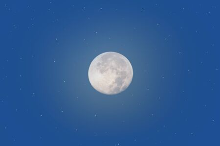 Full moon and stars glowing over classic blue open sky