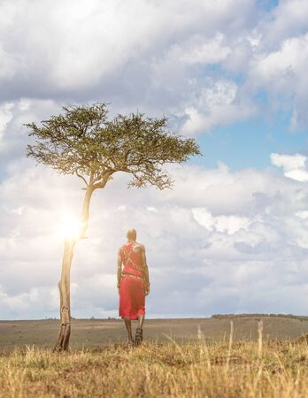 Unidentifiable Maasai tribe man wearing traditional red dress and jewelry facing away and looking out over the Masai Mara National Reserve