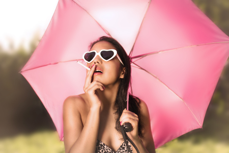 mexican black: Mexican black haired woman smokes in a garden wearing a bikini and protecting herself from the sun with an umbrella