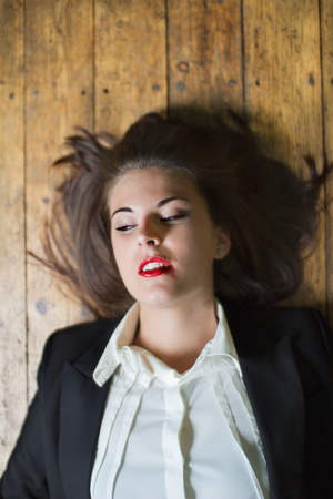 wild hair: Brunette young woman with black suit and red smeared lipstick looking to the side with wild hair Stock Photo