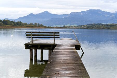 Wooden pier with bench, relaxing jetty in a calm lake with cloudy weather and some mountains and trees in the background.