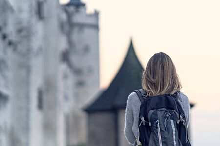 Young female traveler with a backpack standing backward in the fortress of Hohensalzburg in Salzburg during the sunset.