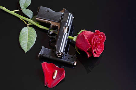 Rose, gun and single bullet on black reflective background