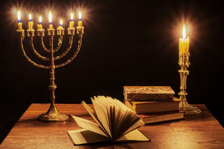 Menorah with seven burning candles, single candlestick and old books.