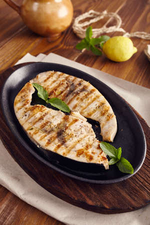 cast iron pan: grilled swordfish slices in a cast iron pan on a wooden table, garnished with mint, oregano, salt and salmoriglio