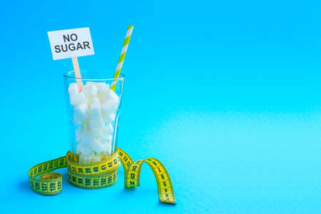 Glass with straw full of sugar cubes with yellow tape. No sugar, cocktail