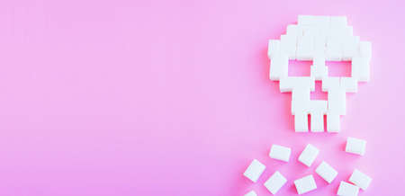 The skull made of sugar cubes. Sugar kills. Pink background Stock Photo