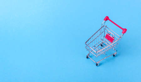 Empty shopping cart with the red handle on a blue background