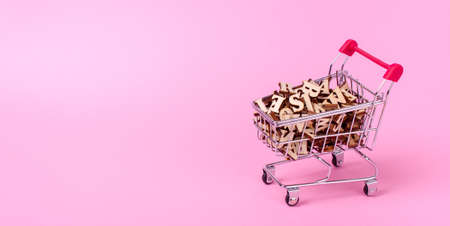 Shopping basket with letters of the alphabet made of wood on a pink background