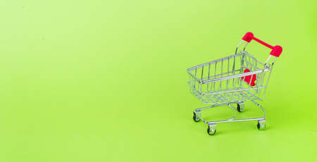 Empty shopping cart with the red handle on a green background Stock Photo