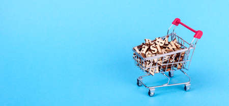 Shopping basket with letters of the alphabet made of wood on a blue background Stock Photo