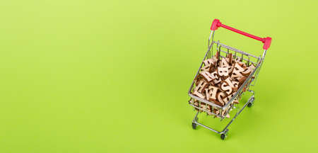 Shopping basket with letters of the alphabet made of wood on a green background Stock Photo