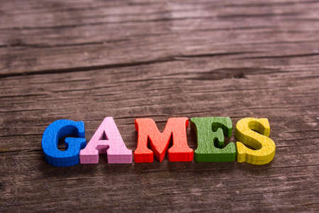 games word made from colored wooden letters on an old table. Concept Stock Photo