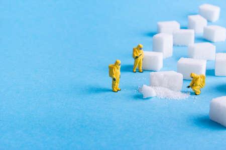 El equipo investiga los terrones de azúcar sobre un fondo azul Foto de archivo - 73923457