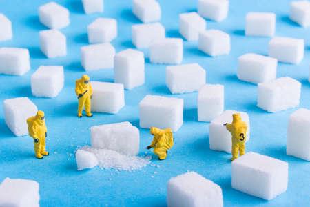 Het team onderzoekt de suikerklontjes op een blauwe achtergrond Stockfoto - 73923383