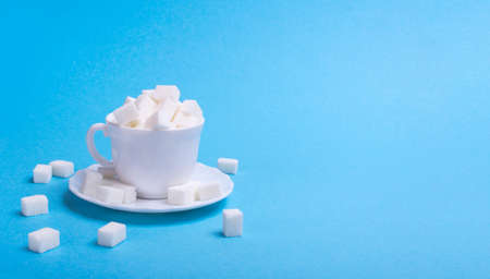 cup filled with sugar cubes to the top. On a blue background