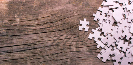 Puzzle pieces with empty space for text on an old wooden table Standard-Bild