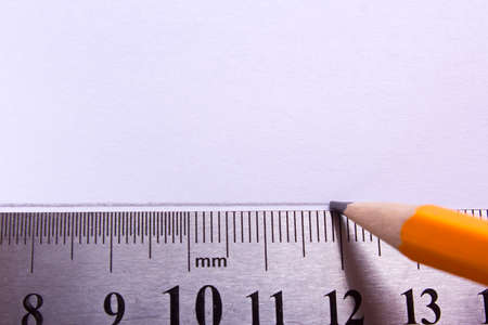 A straight line is drawn in pencil on a white sheet of paper with a ruler. Empty space for text Stock Photo