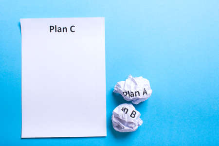 Crumpled paper Plan A B and clean sheet Plan C on a blue background