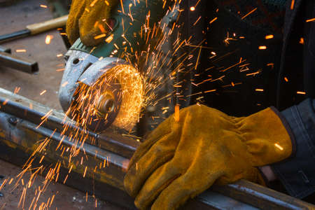 Cutting metal with grinder. Sparks while grinding iron. Man in yellow gloves Фото со стока