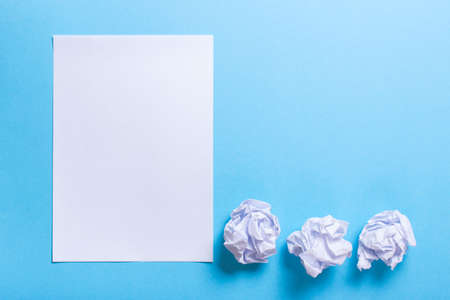 Crumpled paper ball and clean sheet on a blue background Stock Photo