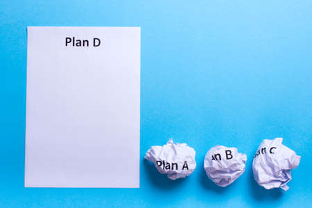 b ball: Crumpled paper Plan A B C and clean sheet Plan D on a blue background