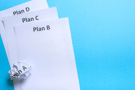Crumpled paper Plan A and clean sheet Plan B C D on a blue background Stock Photo