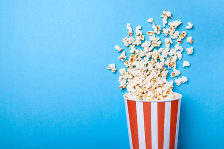 Spilled popcorn and paper bucket in red strip on blue background. Copy space for text Foto de archivo