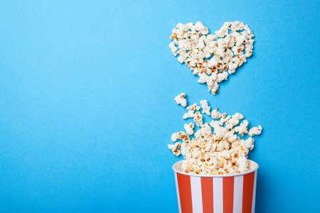 Ich schaue gerne Filme. Verschüttetes Popcorn in Form des Herzens und des Papiereimers in einem roten Streifen auf blauem Hintergrund. Kopieren Sie Platz für Text