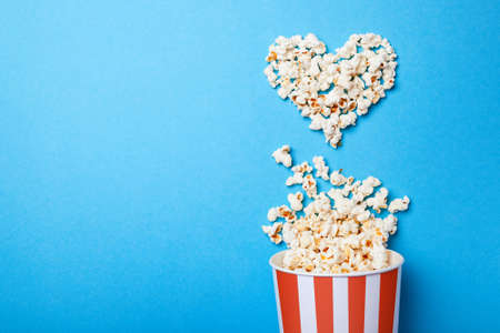 I like watching films. Spilled popcorn in the shape of heart and paper bucket in a red strip on blue background. Copy space for text