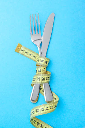 Japanese diet for weight loss. The fork and knife are wrapped in  yellow measuring tape on blue background