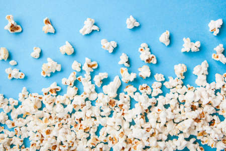 Popcorn scattered on blue background Foto de archivo