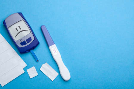 Diabetes mellitus, increased blood sugar in pregnant women. Glucometer and positive test for variability. The display is a sad face. Blue background. Copy space for text