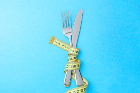 Hunger strike as way to lose weight. The fork and knife are wrapped in yellow measuring tape on blue background Stock Photo