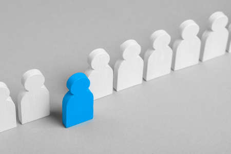 The concept of an initiative employee is leader. From the crowd of white men came out one blue leader 版權商用圖片