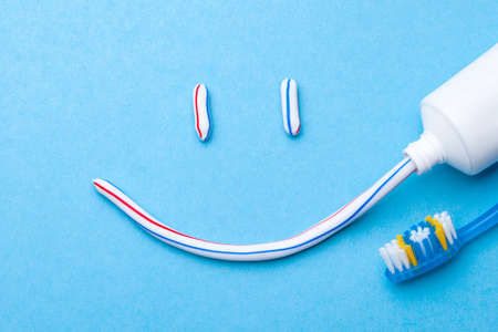 Tooth-paste in the form of face with a smile. Tube of toothpaste and toothbrush on blue background. Refreshing and whitening toothpaste. Stock Photo
